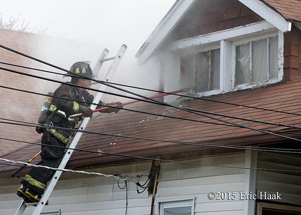firemen venting window from ladder