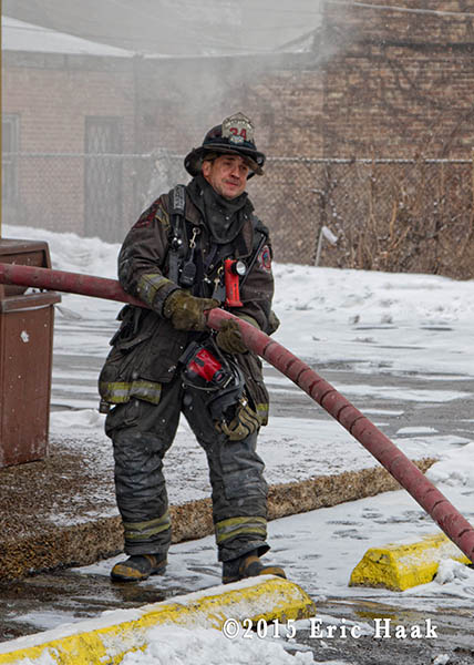 fireman moving charged hose in the winter