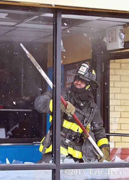 fireman clearing store front windows