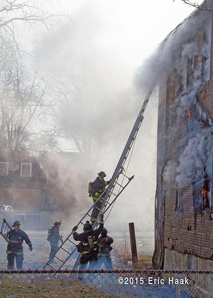 firemen climb ground ladder at smokey house fire
