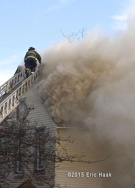 fireman climbs aerial ladder through smoke at house fire