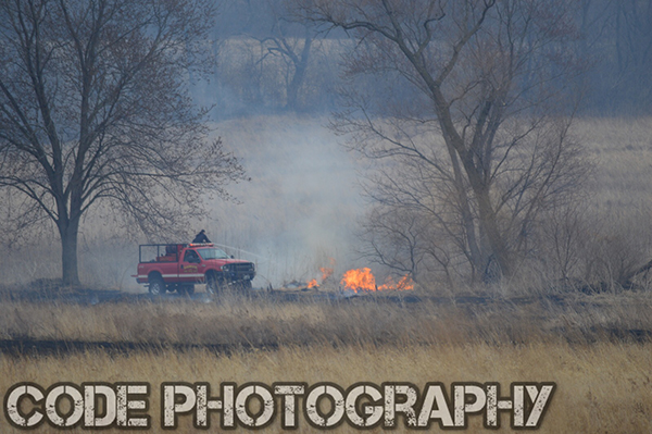 firemen extinguish a grass fire in a field