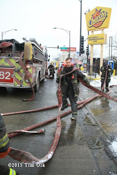 fireman picking up hose after fire