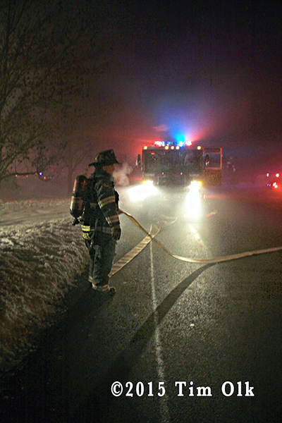 fireman with hose at night fire scene