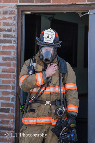 fireman at fire scene with PPE using radio