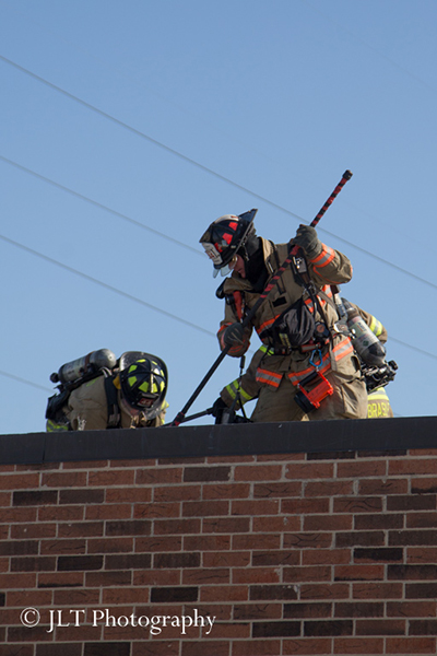 firemen on roof of commercial building