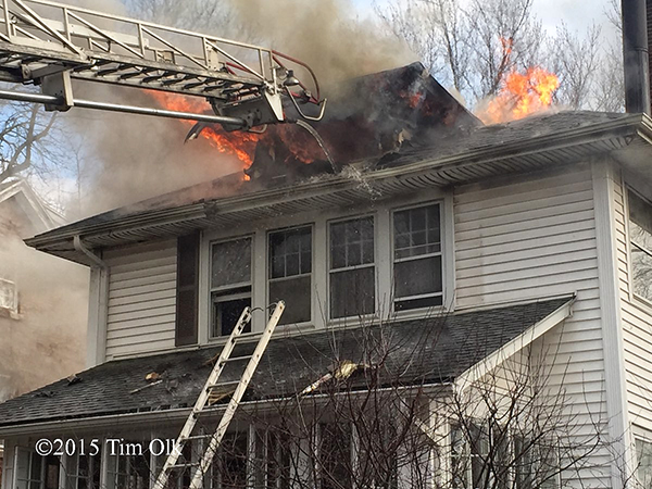 fire burns through the roof of a house