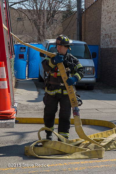 fireman pulling hose from fire engine