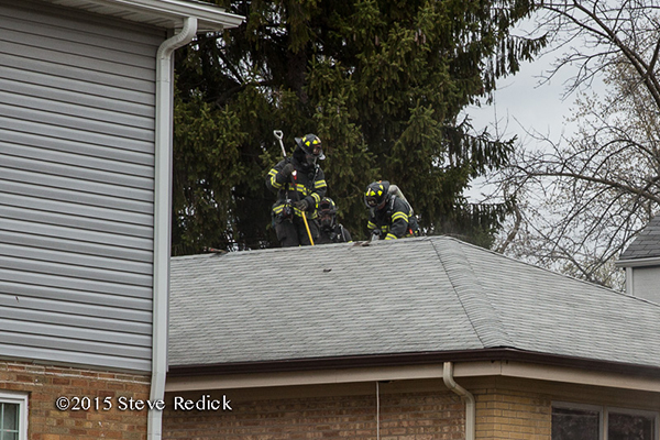 firemen vent roof of a house