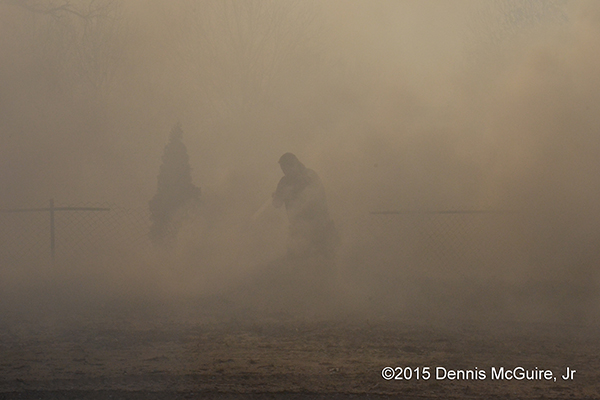 firemen enveloped in smoke fighting brush fire