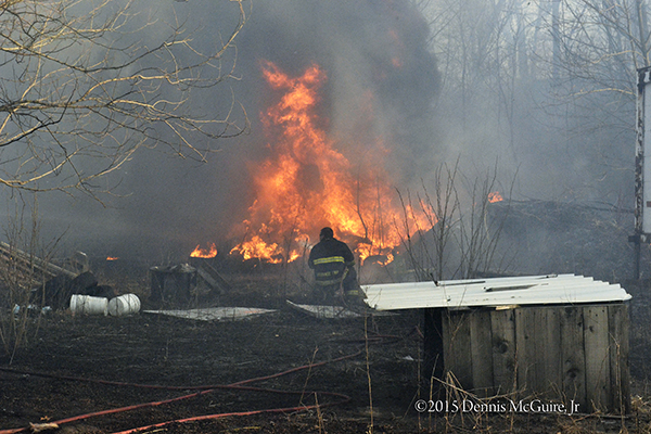 brush fire enters junk yard