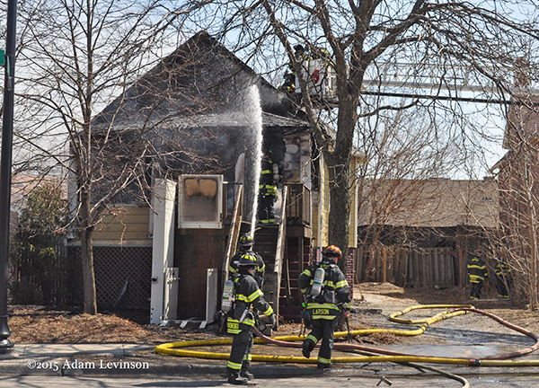 firemen operate a hose during a house fire