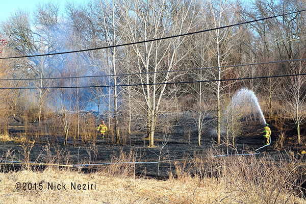 fireman with hose after brush fire