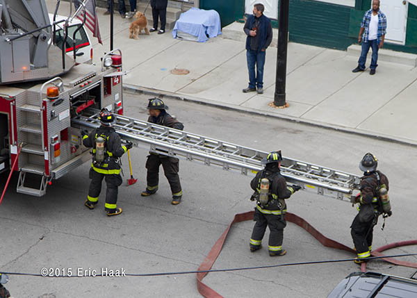 firemen remover ground ladder from fire truck