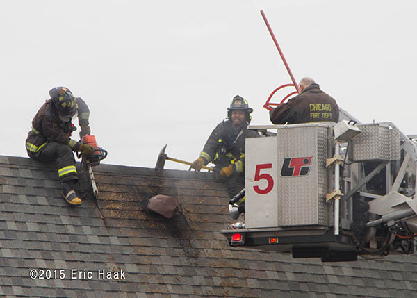 firemen venting peak roof at a fire