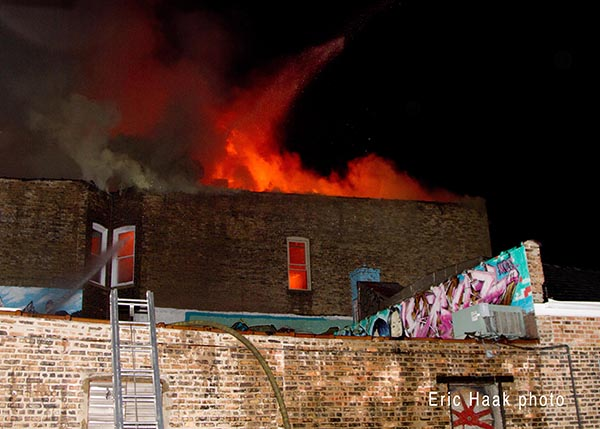 flames through roof of apartment building at night