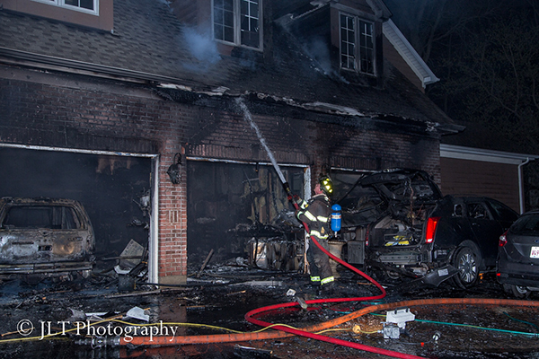 fireman with hose line at house fire