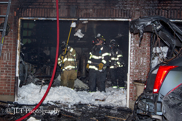 firemen overhaul garage after fire