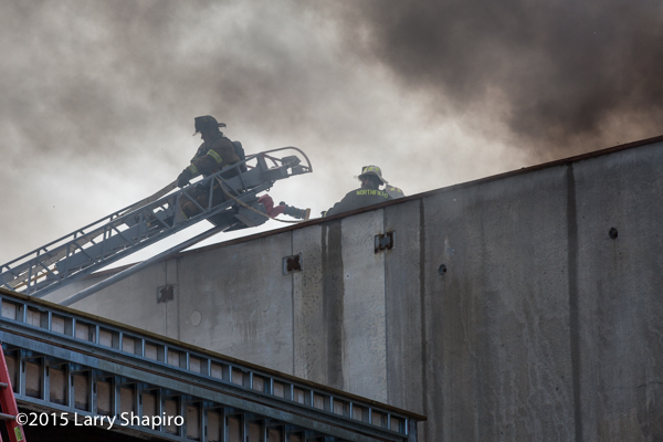 fireman on aerial ladder with dark smoke