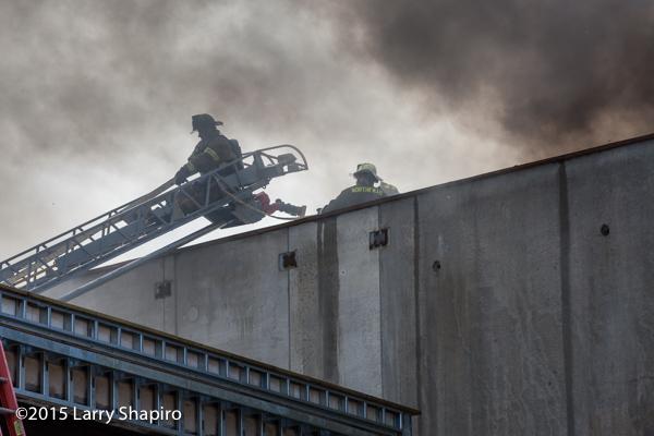 fireman on aerial ladder with dark smoke