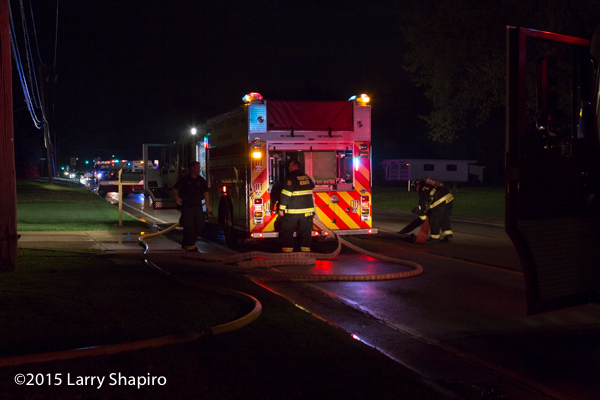 firemen pull hose from an engine at night
