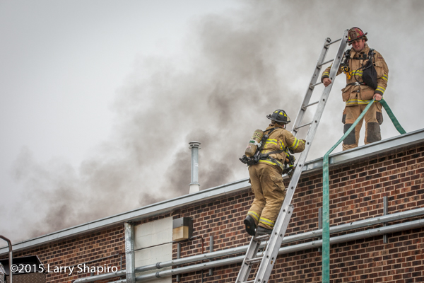 firemen climb ladder to roof with smoke