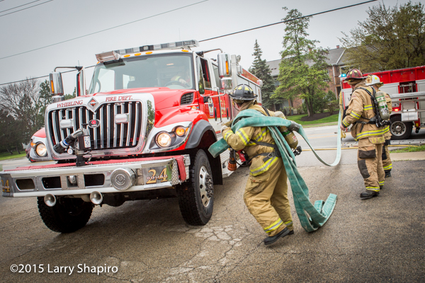 fireman pulls hose at fire scene