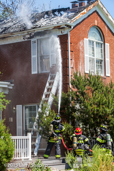 firemen apply foam during house fire
