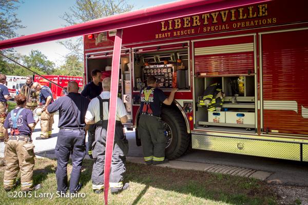 firemen fill air bottles at fire scene