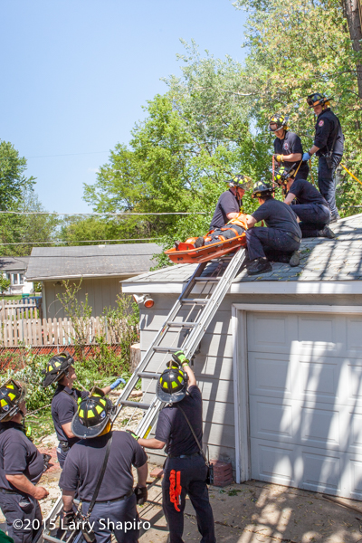 firemen rescue a tree worker that fell onto a roof