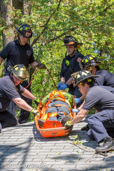 firemen remove an injured worker in a stokes basket
