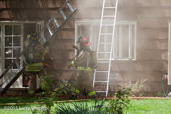 firemen raise ground ladder at house ire