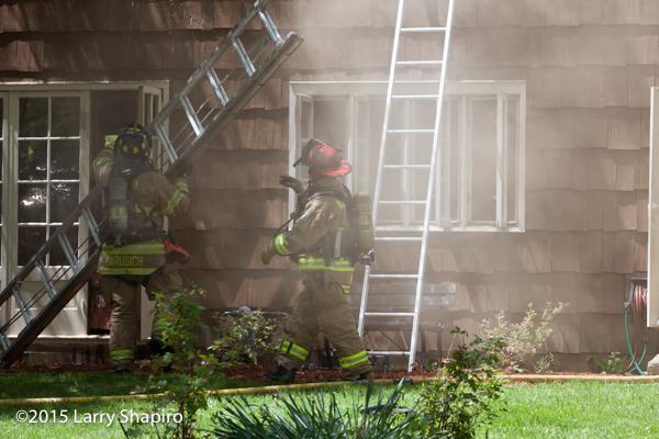 firemen raise ground ladder at house ire