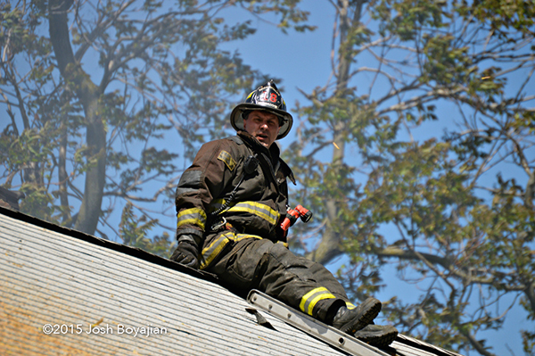 fireman on the roof of a house
