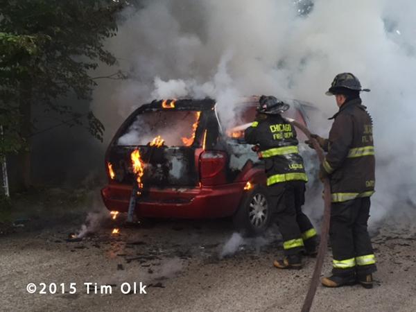 firemen extinguish a minivan engulfed in flames