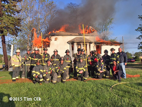 firemen pose with burning house
