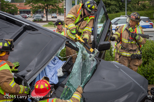 fireman uses ax to cut windshield