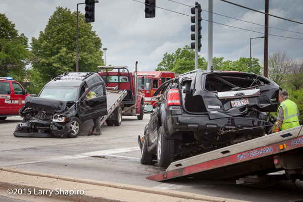 wrecked SUVs loaded onto tow trucks