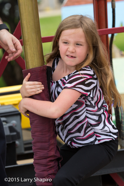 young girl sliding a fire pole