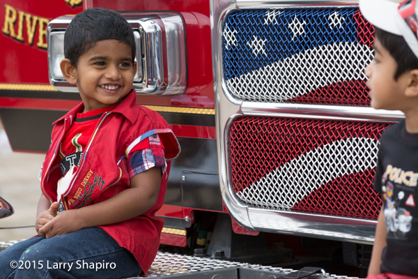 young Indian boy sitting on a fire truck