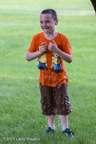 boy getting soaked with hose
