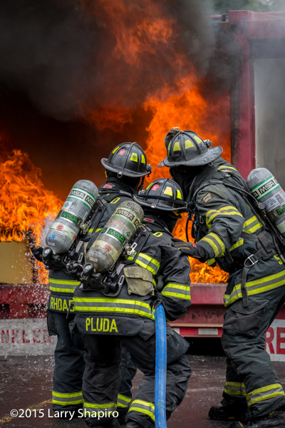 firemen approaching flames with hose line