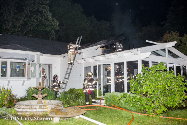 firemen overhaul house after fire at night