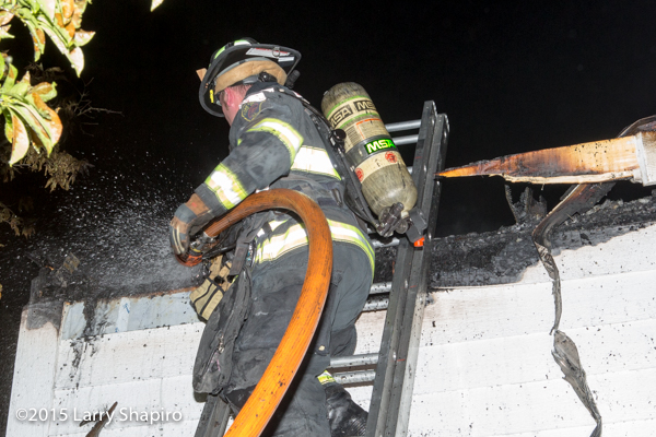 fireman on ladder using hose at night