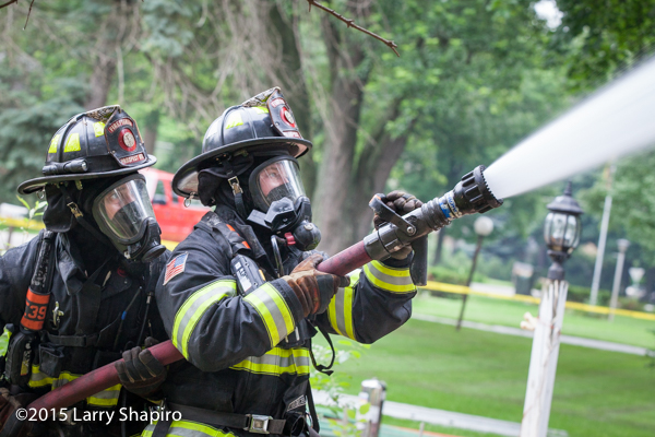 firemen operate hose line