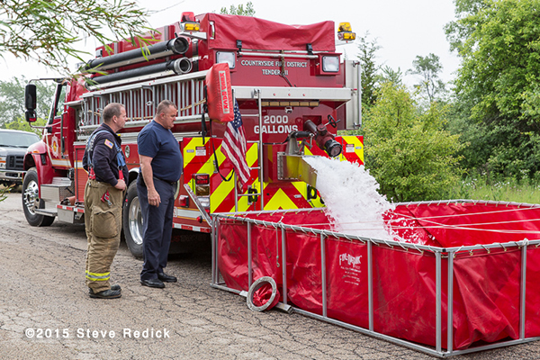 fire departmetn water tender dumping into a portable tank