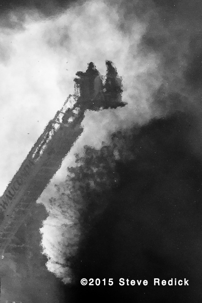 firemen in tower ladder with smoke