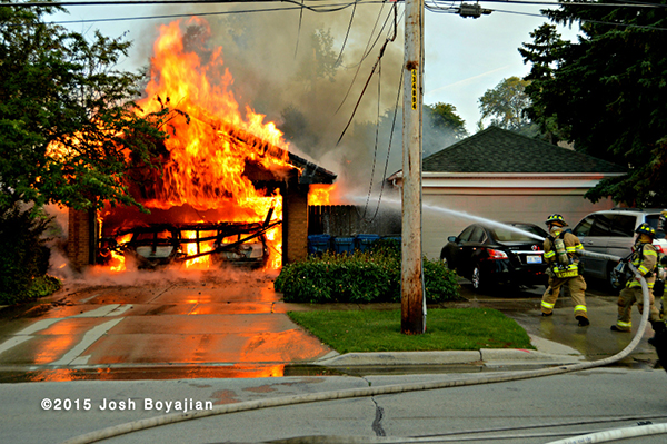 firemen battle a garage fully engulfed in flames