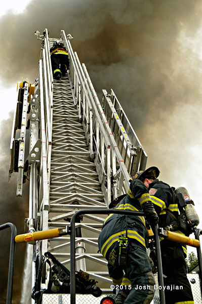 fireman climbs E-ONE aerial ladder