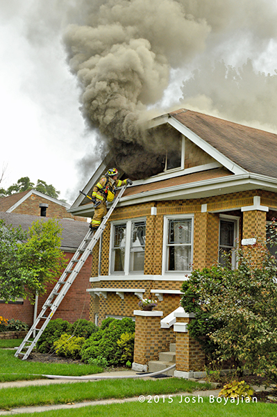 heavy smoke from the attic of a house on fire